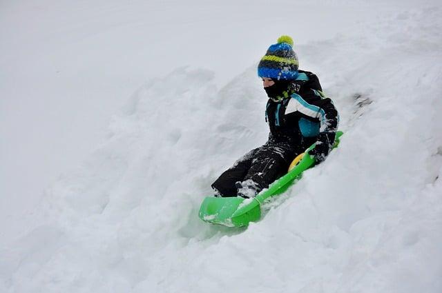 enfant faisant de la luge dans la neige
