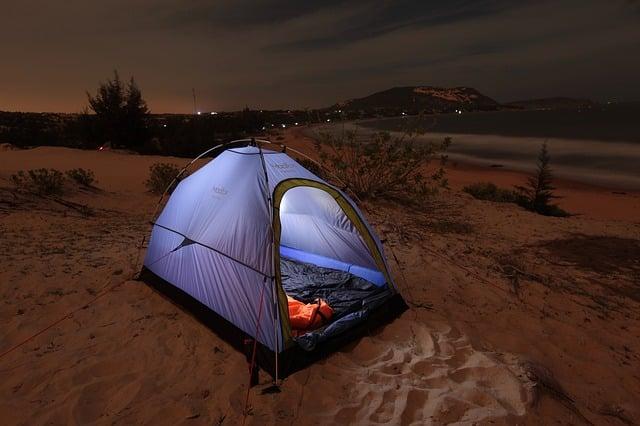 personne dormant dans sa tente de plage la nuit